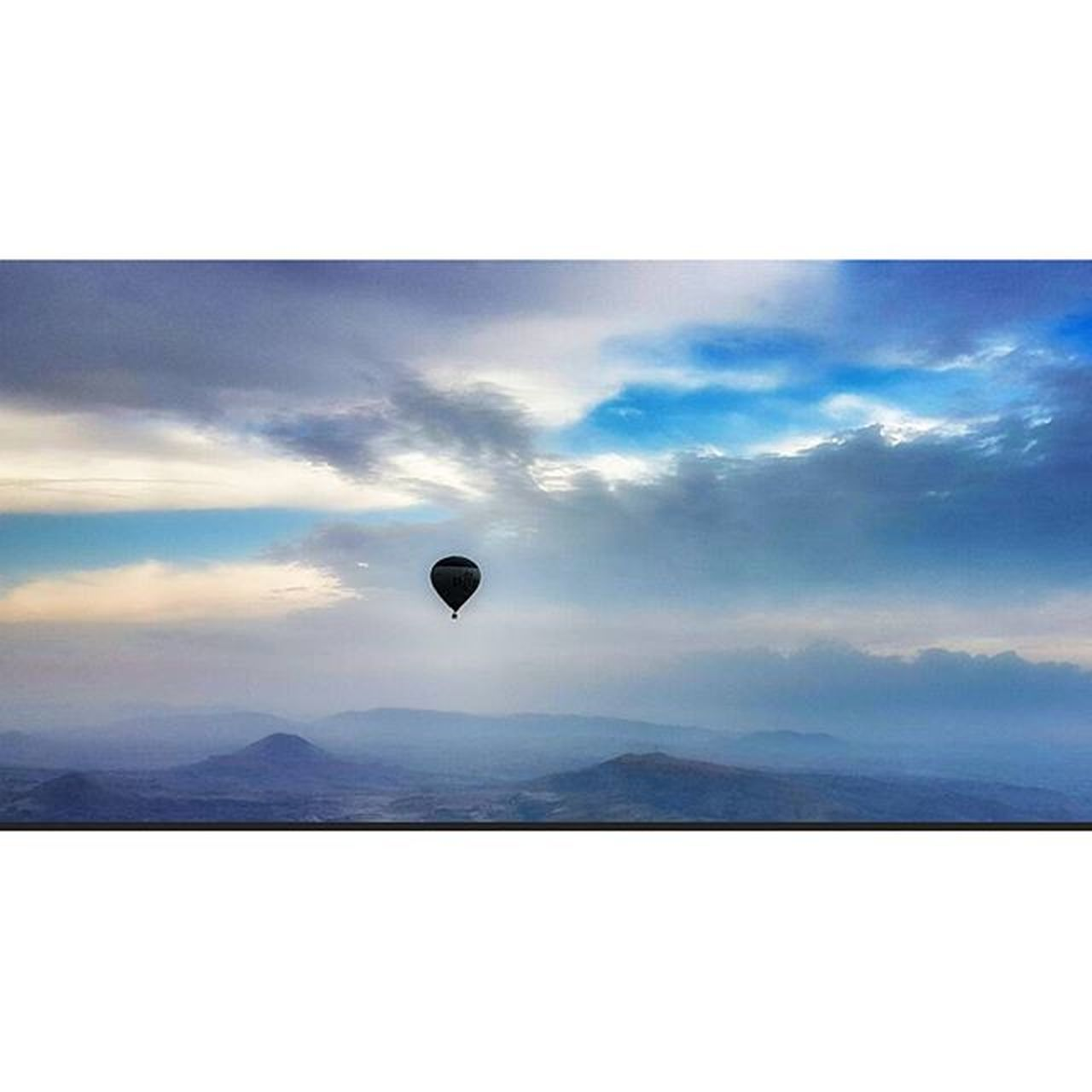 sky, cloud - sky, mid-air, nature, scenics, tranquil scene, beauty in nature, outdoors, mountain, day, adventure, tranquility, flying, one person, hot air balloon, people