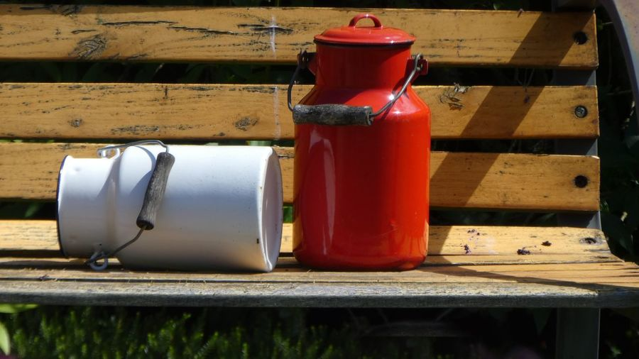 Close-up of milk canisters on wooden bench