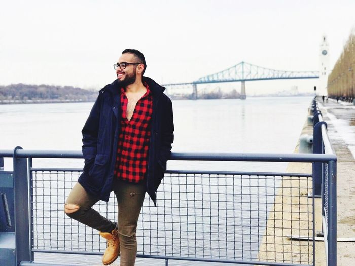 Bridge - Man Made Structure Railing Real People Lifestyles One Person Young Adult River Young Men Casual Clothing Water Outdoors Sky Leisure Activity Front View Day Transportation Full Length Suspension Bridge Standing Eyeglasses  Beard