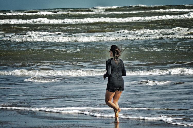 Rear view full length of woman jogging at beach