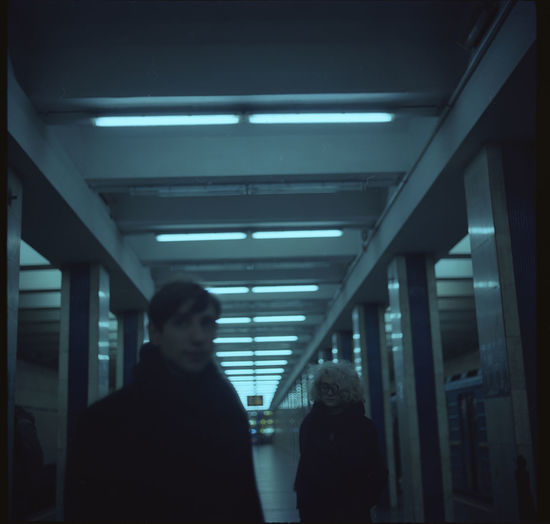 Rear view of silhouette man and woman walking in illuminated building