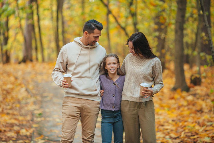 Full length of father with daughter against trees during autumn