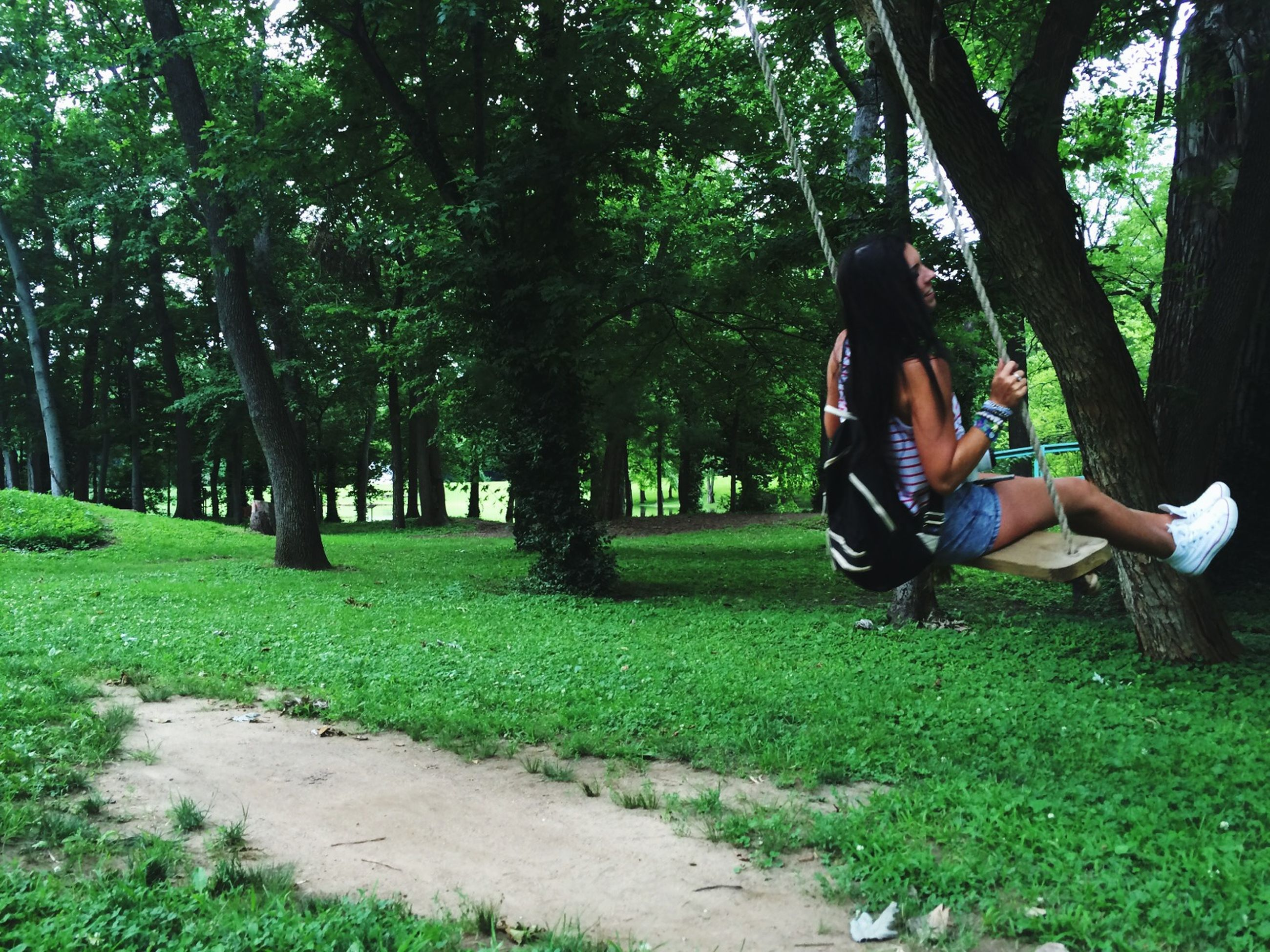 tree, lifestyles, leisure activity, grass, men, full length, green color, person, casual clothing, growth, park - man made space, sitting, tree trunk, rear view, nature, day, togetherness