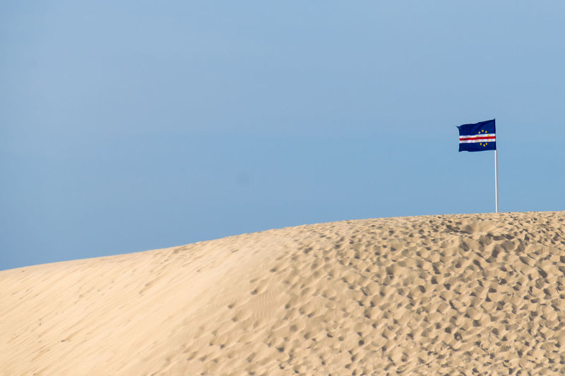 Cape Verde Flag Arid Climate Beauty In Nature Blue Clear Sky Day Desert Flag Landscape Nature No People Outdoors Patriotism Sand Sand Dune Scenics Sky
