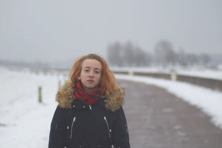 Portrait of woman standing on road during snowfall