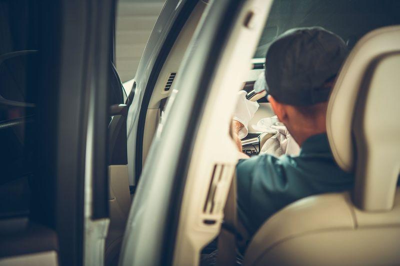 Man cleaning car dashboard