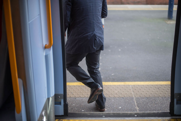 Low section of man running out the bus