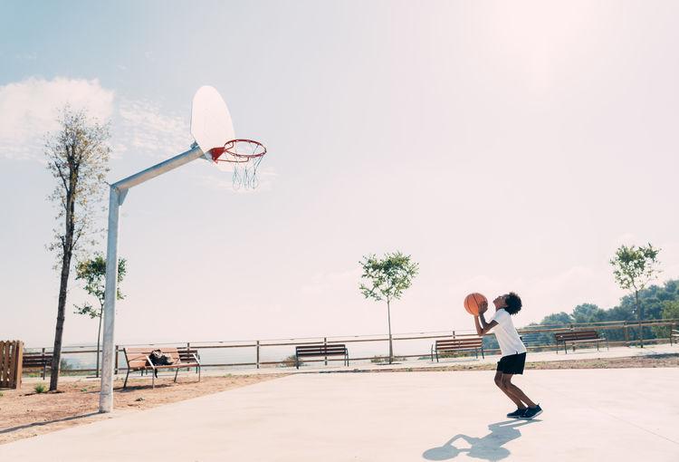Man playing basketball hoop against sky