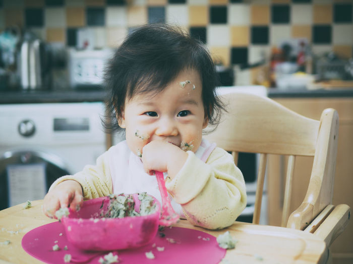Portrait of cute girl eating food at home