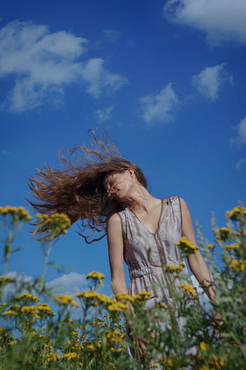 Low angle view of woman tossing hair while standing at field