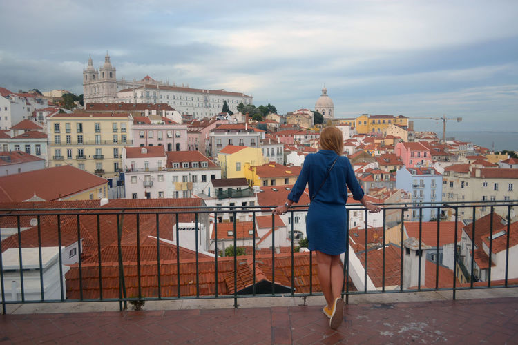 Rear view of woman standing by railing against cityscape