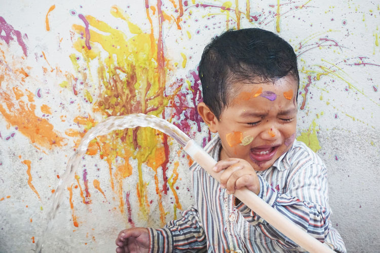 Crying boy holding garden hose while painting wall