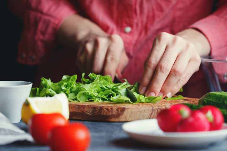 Chopping Close-up Cutting Cutting Board Food Food And Drink Freshness Healthy Eating Holding Human Hand Indoors  Kitchen Kitchen Knife Lifestyles Making Midsection One Person Preparation  Preparing Food Real People Salad Selective Focus Table Tomato Vegetable