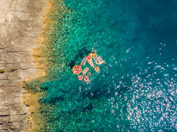 Aerial view of people relaxing on sea during sunny day