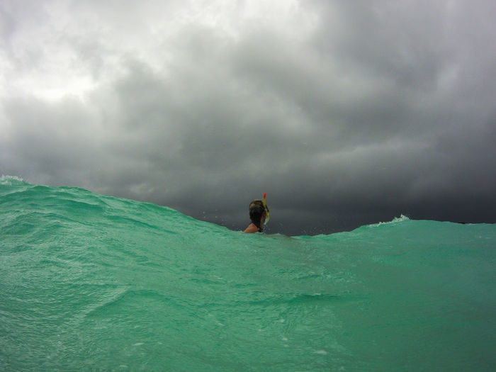 Woman snorkeling in sea against storm clouds