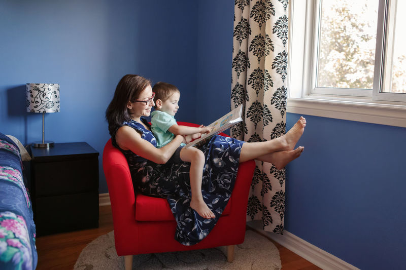 Mother with son boy sitting  at home and reading book. child kid early development education
