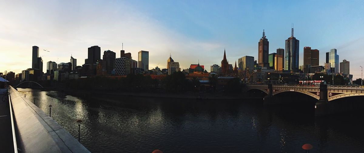 City Skyline By River Against Sky