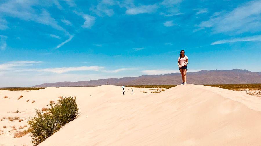Teenage girl standing at desert on sunny day