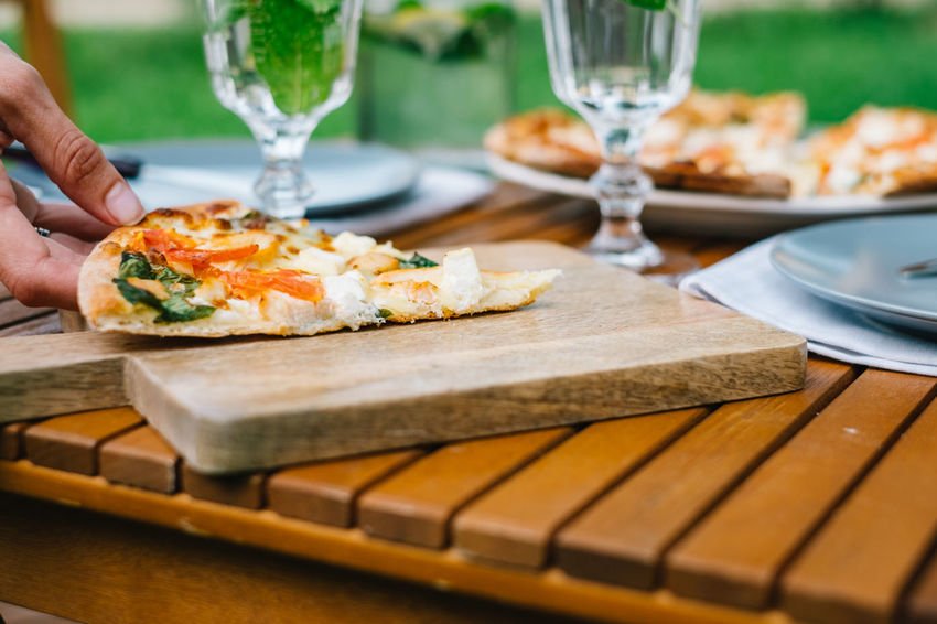 slice of italian pizza Food And Drink Human Body Part Food Freshness Human Hand Bread One Person Ready-to-eat Pizza Slice Of Pizza Eating Utensil Cutting Board Copy Space Table Knife Selective Focus Healthy Eating Close-up Dairy Product Table Cheese Food And Drink Glass Vegetable Rustic Picnic