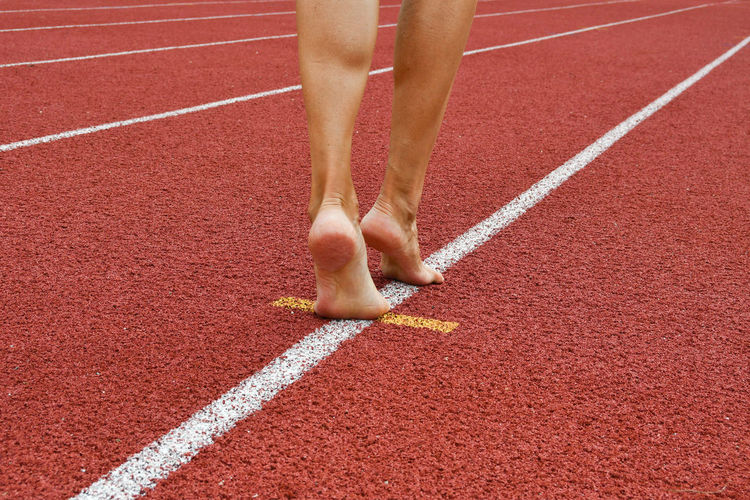 Low section of woman walking on sports track