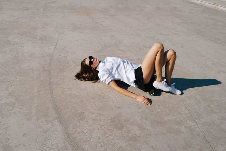 Young Adult Lying Down Relaxation Young Women Lying On Back Lifestyles Beautiful Woman Women Casual Clothing High Angle View Leisure Activity Summer Concrete Floor Concrete Jungle Casual Casual Look Woman Portrait Female Girl Girls Sport Fun Having Fun Shirt