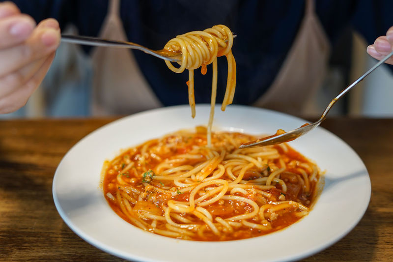woman eating spaghetti tomato sauce Eating Spaghetti Chopsticks Close-up Eating Utensil Finger Food Food And Drink Freshness Hand Holding Human Hand Italian Food Kitchen Utensil One Person Pasta Plate Ready-to-eat Real People Serving Size Spaghetti Spaghetti Tomato Sauce Spoon Table Unrecognizable Person