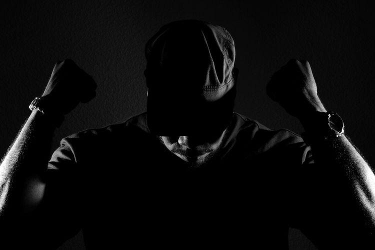 Muscular man wearing cap against wall in darkroom
