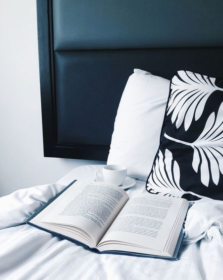 High Angle View Of Book With Cup And Cushions On Bed