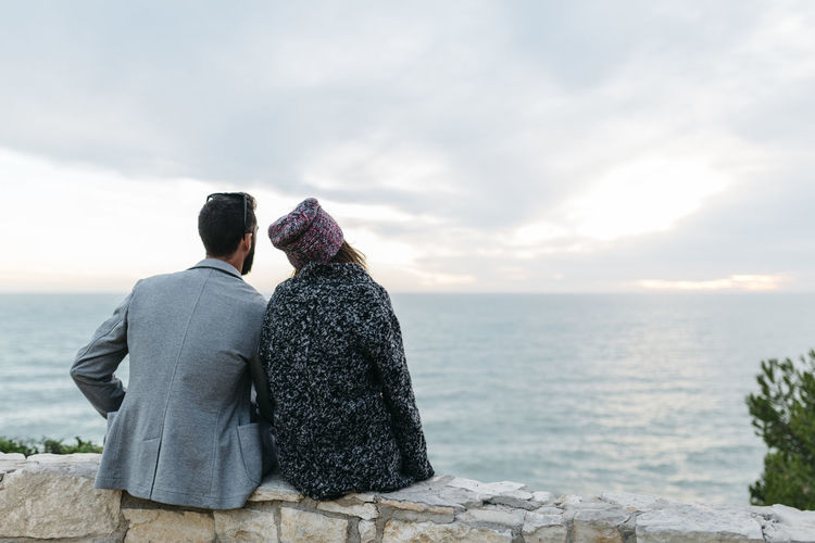 Rear View Of Couple Sitting On Retaining Wall By Sea