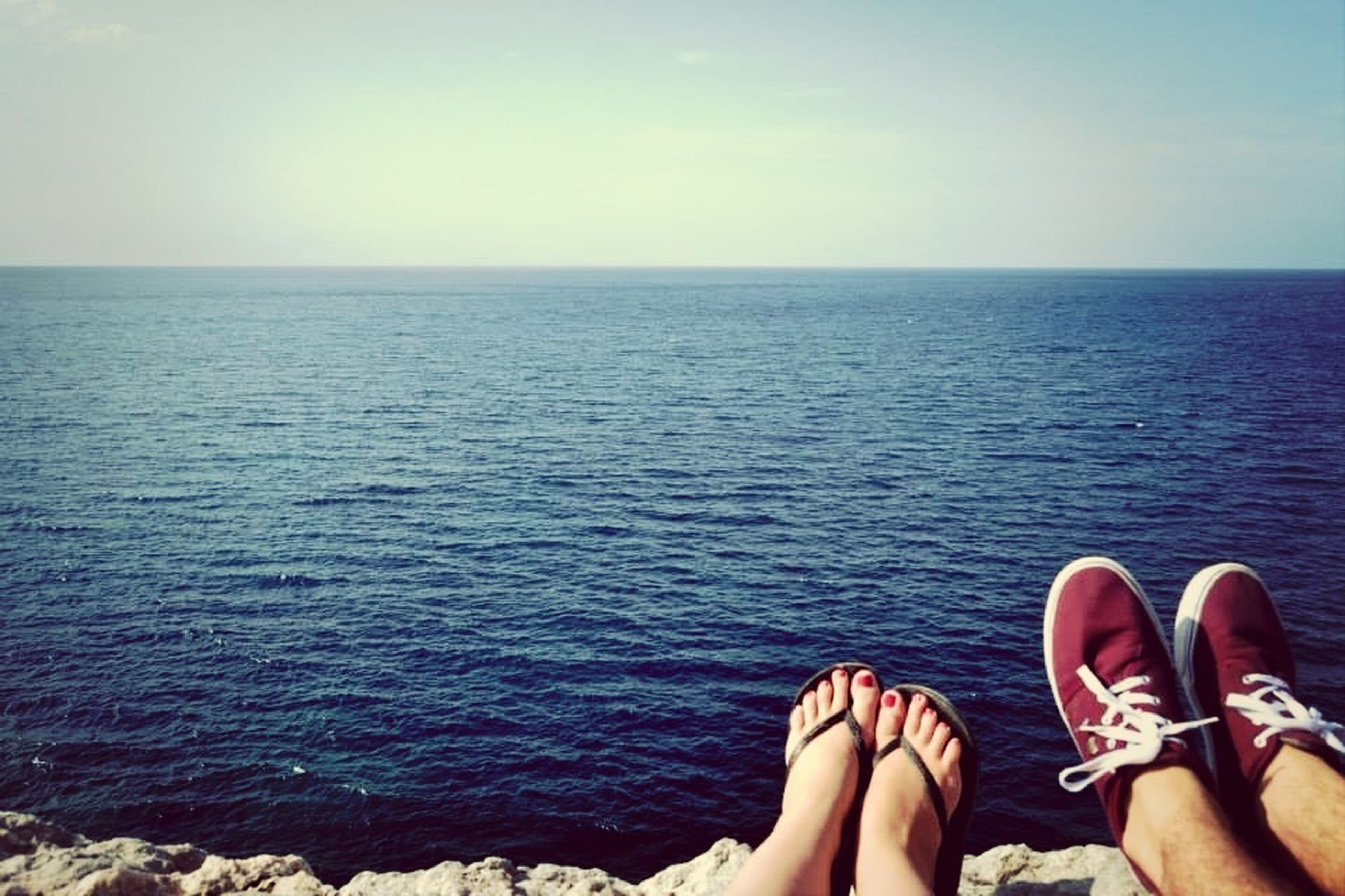 water, sea, horizon over water, lifestyles, leisure activity, low section, scenics, tranquil scene, part of, person, tranquility, sky, personal perspective, beauty in nature, rippled, nature