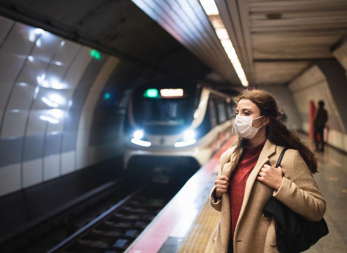 Woman wearing mask standing on railroad station platform