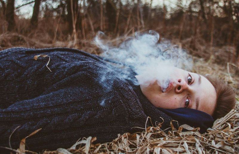 Portrait of a handsome teenage boy with smokes