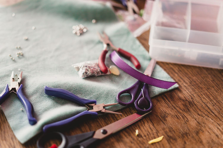 Craft Items Craftsmanship  Vintage Craft Arts And Crafts Table Still Life Selective Focus Close-up Wood - Material No People Scissors Indoors  Hand Tool Work Tool High Angle View Tool Focus On Foreground Equipment Art And Craft Nature Metal Purple Personal Accessory