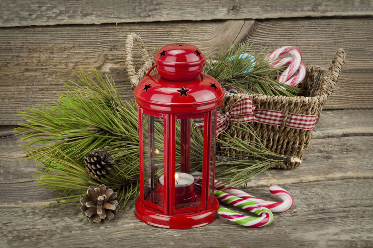 Red lantern and wicker basket with candy canes on wooden table