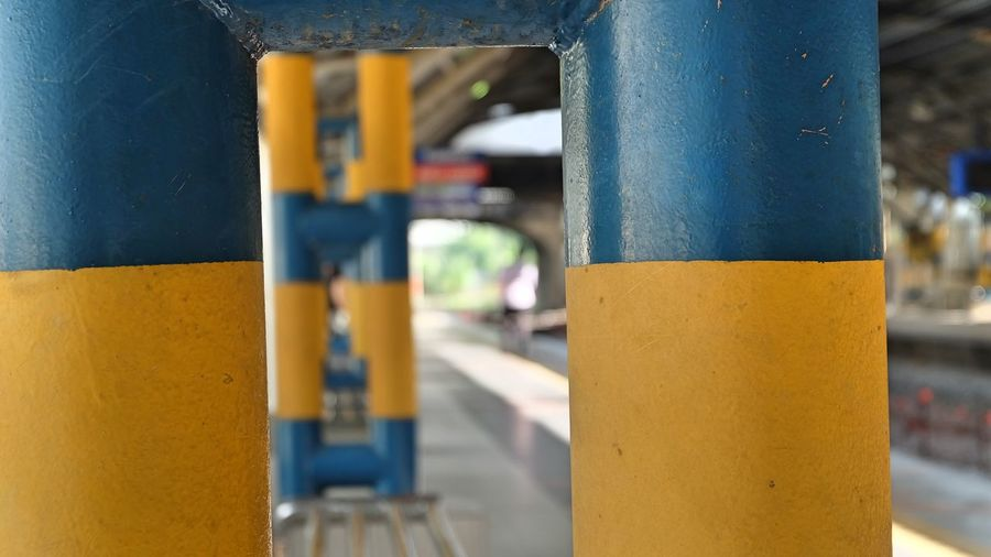 Close-up of yellow metal pole against wall