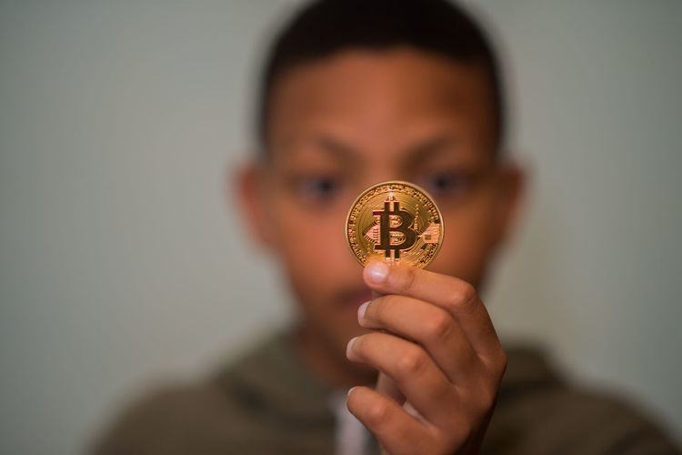 Close-up of boy holding bitcoin