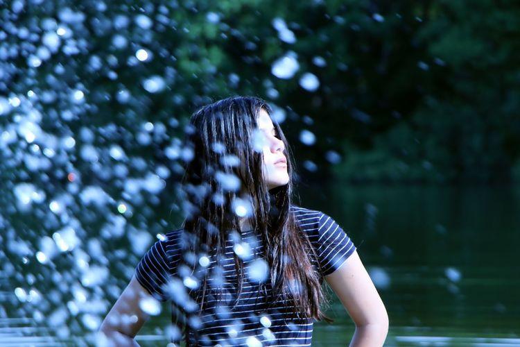 Water splashing on woman standing in lake