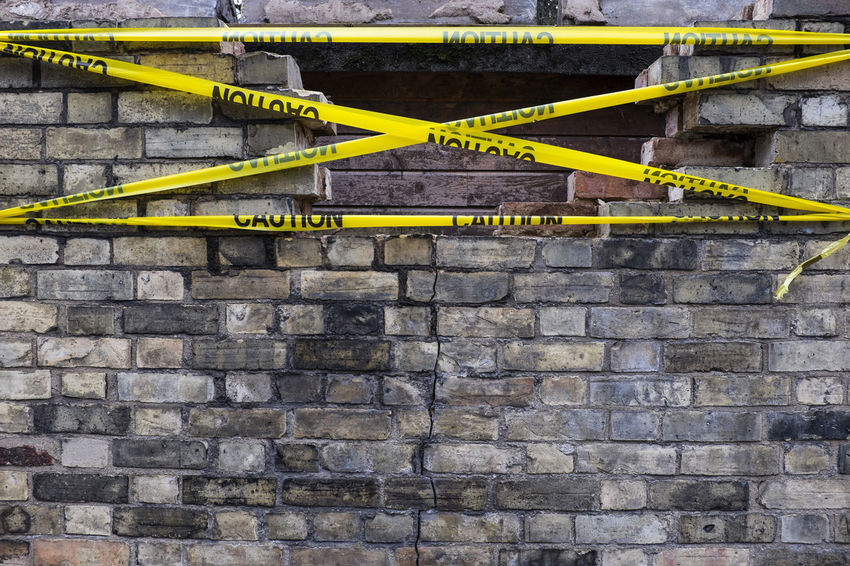 """Tape carrying the word """"Caution"""" covers section of missing wall. Quite what the tape will do is unclear aside from warn people. Brick Wall Brick Wall Bricks Building Exterior Built Structure Caution Cracked Damaged Damaged Wall Danger Dangerous No People Outdoors Tape Wall"""