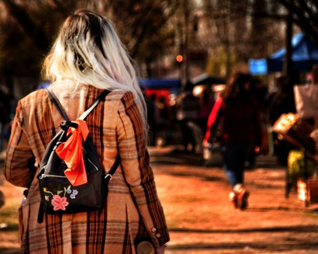 Rear view of woman carrying backpack while walking on street in city