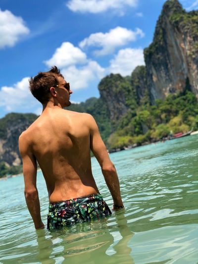 Rear view of shirtless man standing in river against sky