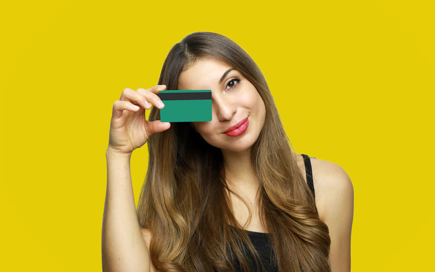 Portrait of happy young woman holding credit card against yellow background