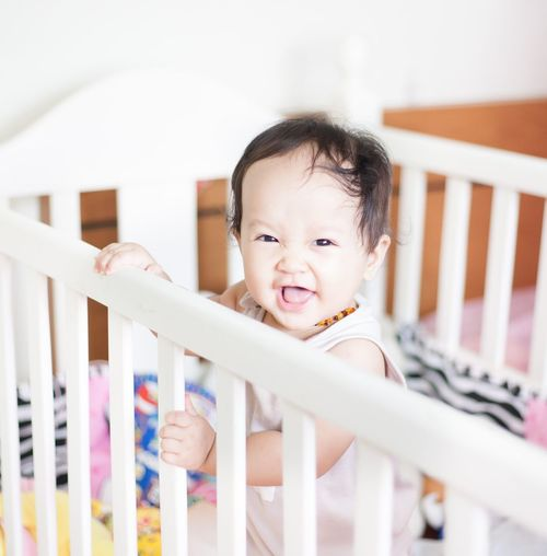 Portrait of smiling baby girl in crib at home