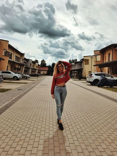 Full length portrait of young woman in city against sky