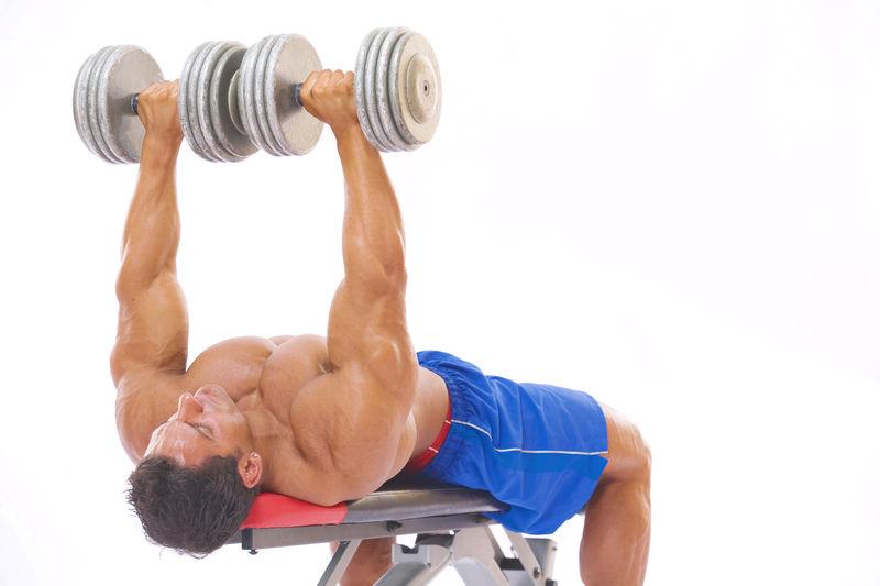 Shirtless man exercising against white background