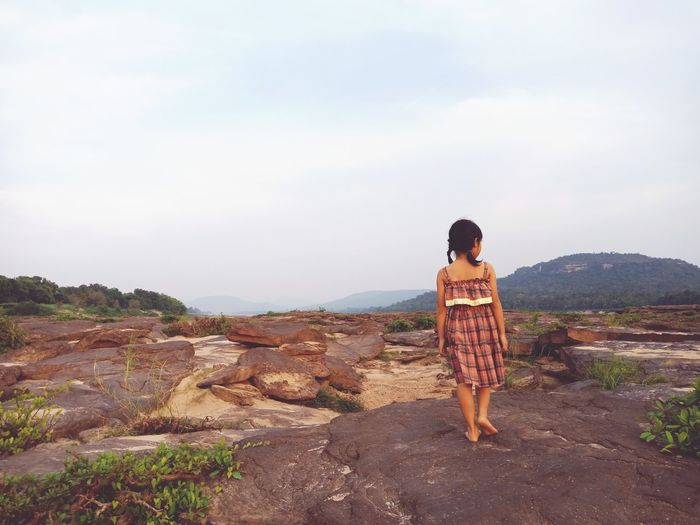 Rear view of girl standing on rock against sky