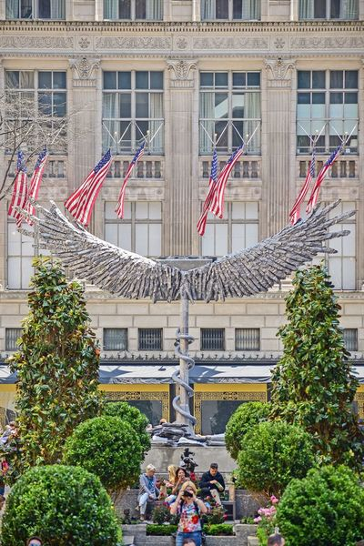 Rockerfellercenter Wings Wings Art Display Architecture Built Structure Building Exterior Flag Plant Day Group Of People Nature Outdoors Large Group Of People Travel Destinations Building Patriotism Real People City Women Tree Independence
