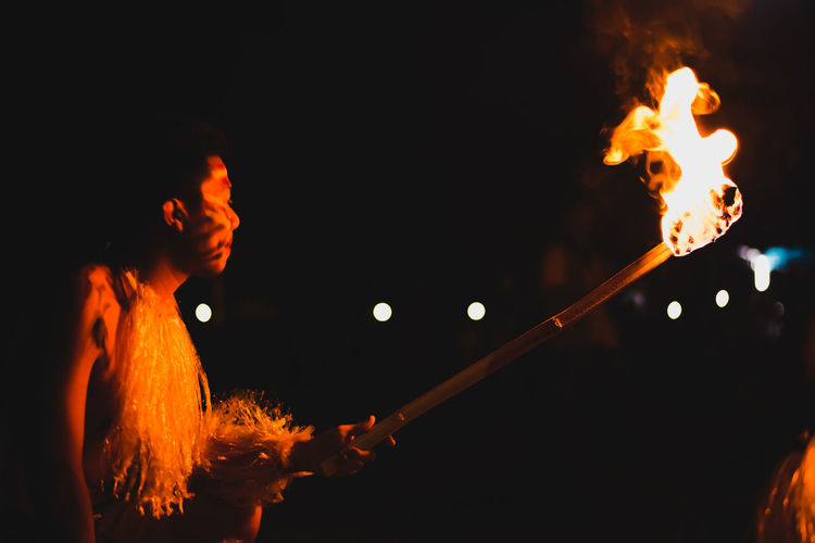 Man holding burning stick at night