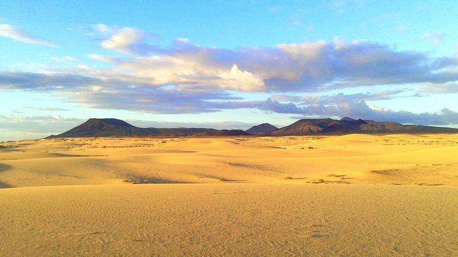 Scenic view of desert against dramatic sky