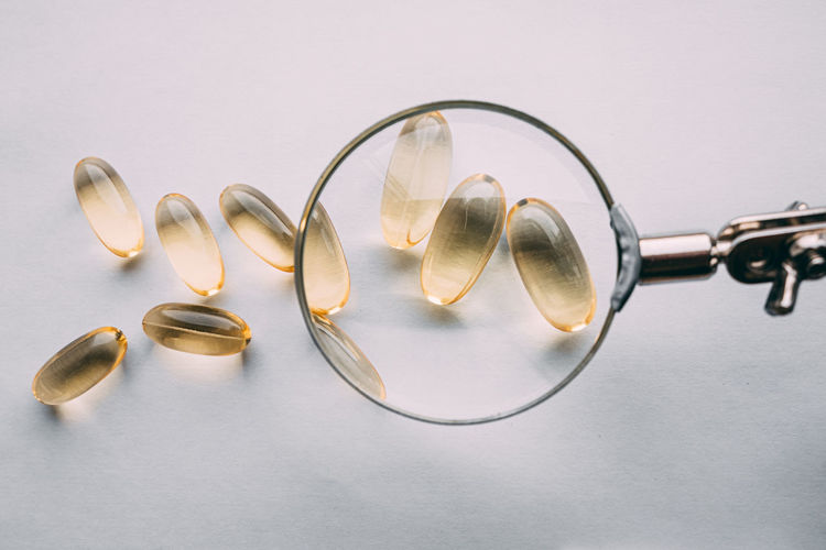 Yellow transparent omega 3 capsules under a magnifying glass. food additive development concept
