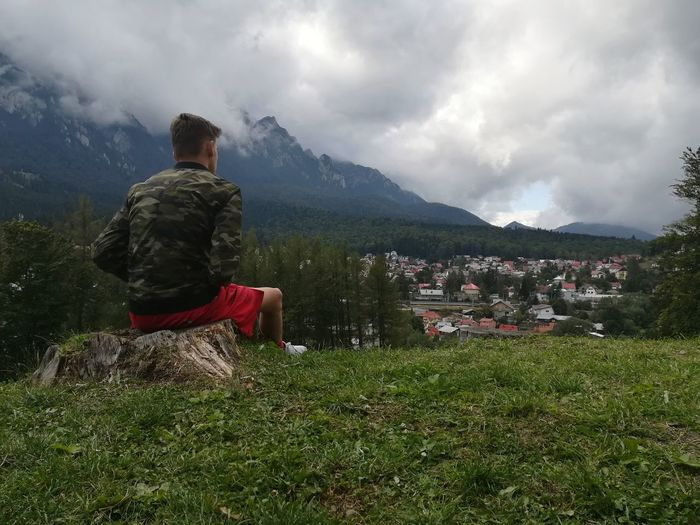Rear view of man sitting on landscape against cloudy sky